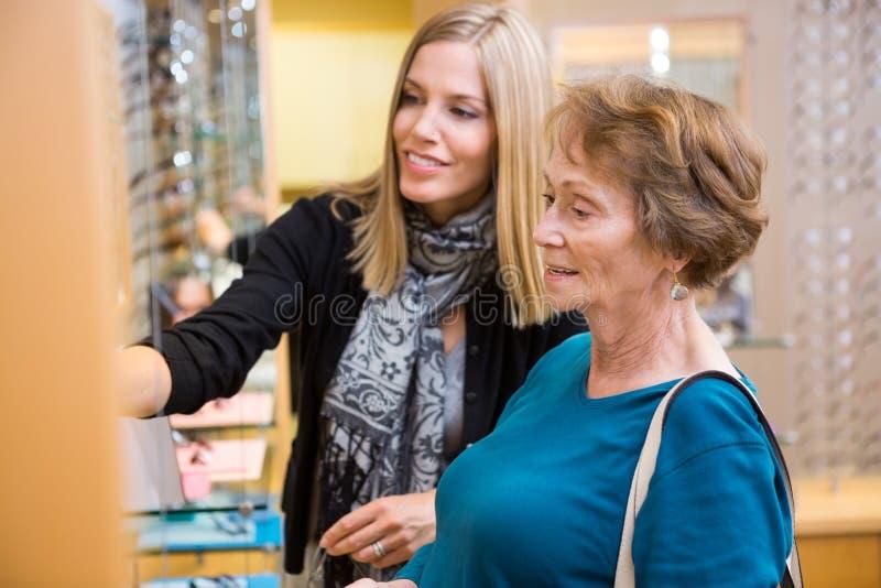 Salesgirl помогая старшему клиенту в выбирать стоковое фото