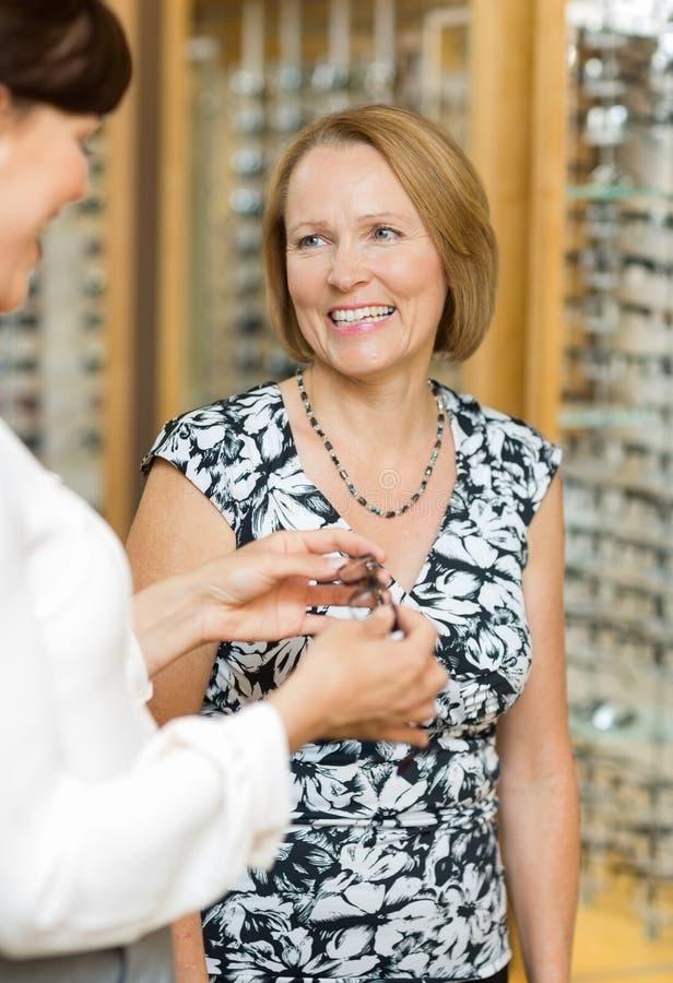 Salesgirl Assisting Senior Customer In Selecting stock photo