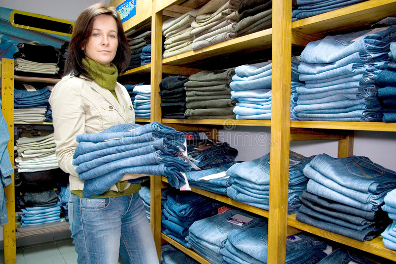 Saleslady in a jeans wear shop. The saleslady holding a few pairs of blue jeans, shelves with lots of them