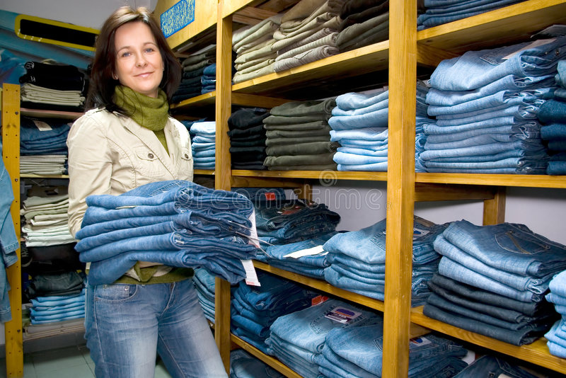 Saleslady in jeans wear shop. A saleslady holding a few pairs of blue jeans, shelves with lots of them royalty free stock image