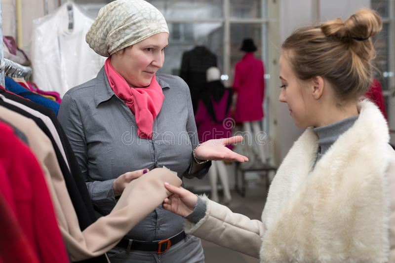 Saleslady showing Variety of Jackets to Customer in Retail Store. Saleslady in Uniform showing Variety of Winter and Spring Jackets to young Female Customer in stock image