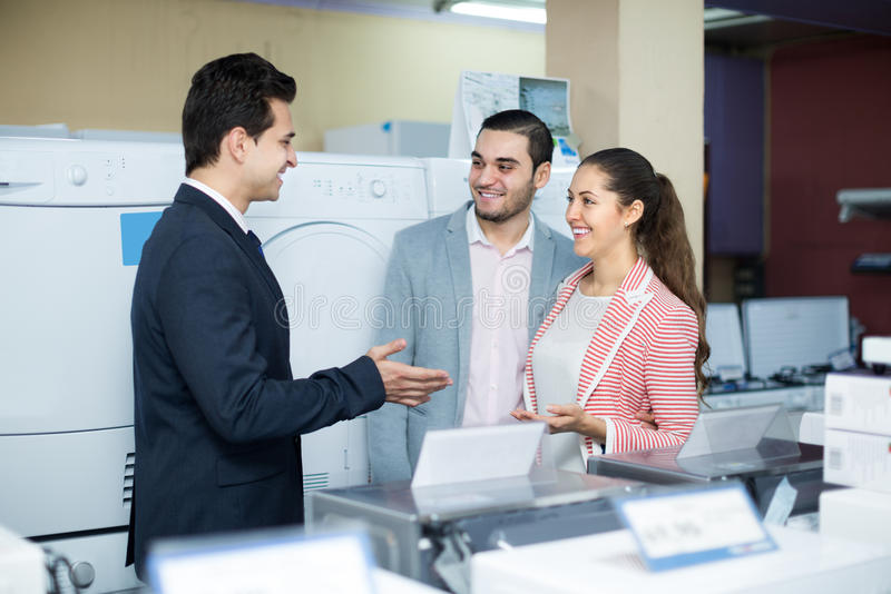 Salesman and adult customers in store stock photos