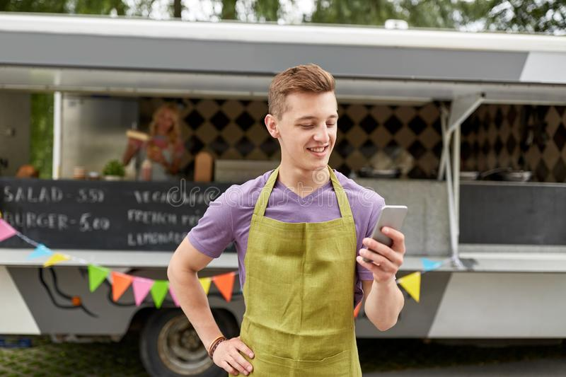 Salesman in apron with smartphone at food truck. Street sale, technology and people concept - happy young salesman in apron with smartphone at food truck royalty free stock photos