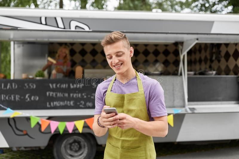 Salesman in apron with smartphone at food truck. Street sale, technology and people concept - happy young salesman in apron with smartphone at food truck royalty free stock photo