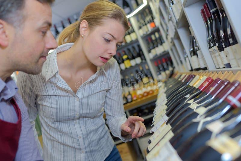 Salesman assisting female customer in choosing wine. Choosing stock photo