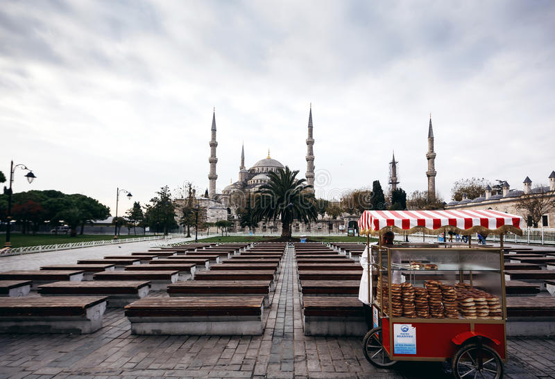 Salesman of baked bagels with little truck. ISTANBUL, TURKEY - NOVEMBER 28: Salesman of baked bagels with little truck in front of Famous Sultan Ahmed Mosque ( stock photography