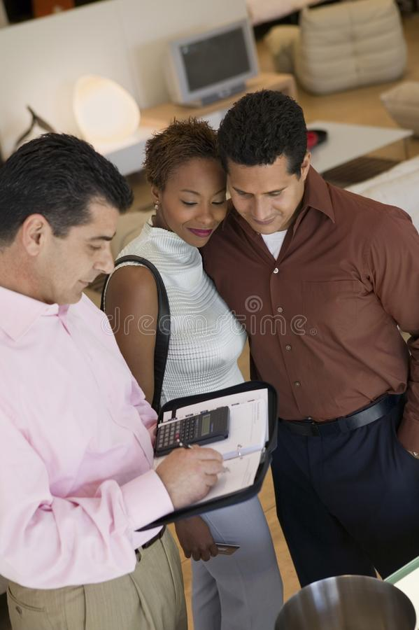 Download Salesman Calculating Purchase Amount Of Couple Stock Photo - Image: 13584248