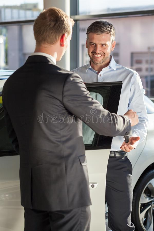 Salesman in car dealership. Image of salesman in car dealership giving keys to client royalty free stock photos