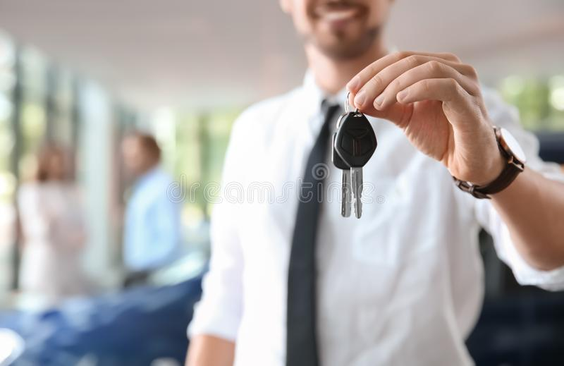 Salesman with car keys in auto dealership. Closeup stock photo