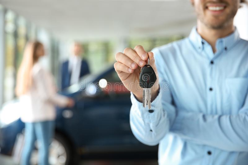 Salesman with car keys in modern auto dealership. Closeup stock photography