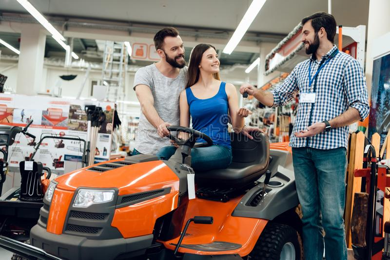 Salesman is showing couple of clients new cleaning machine in power tools store. Salesman in checkered shirt is showing couple of clients new cleaning machine stock image