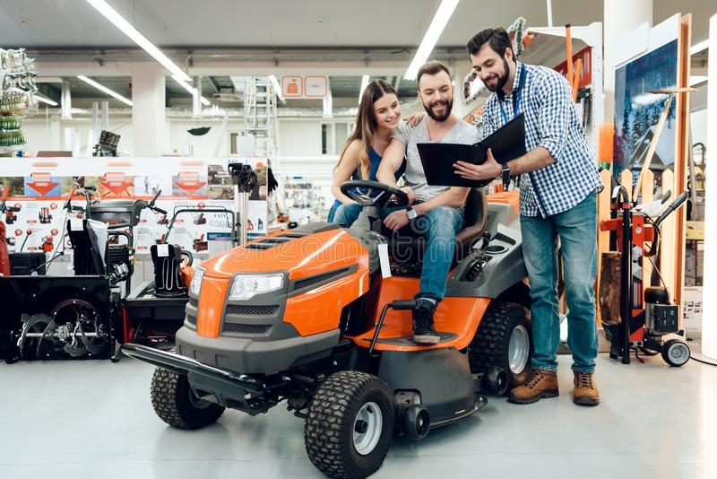 Salesman is showing couple of clients new cleaning machine in power tools store. Salesman in checkered shirt is showing couple of clients new cleaning machine stock photo