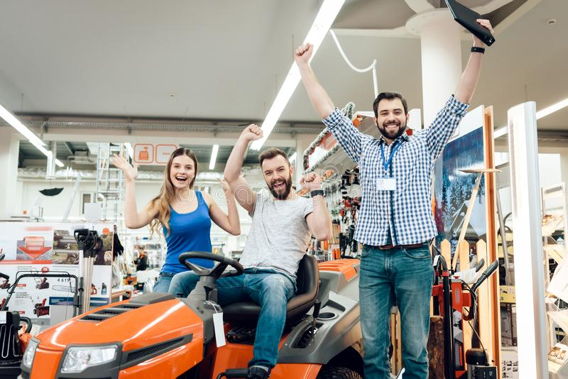 Salesman is showing couple of clients new cleaning machine in power tools store. Three people celebrating new purchase. Salesman in checkered shirt is showing stock images