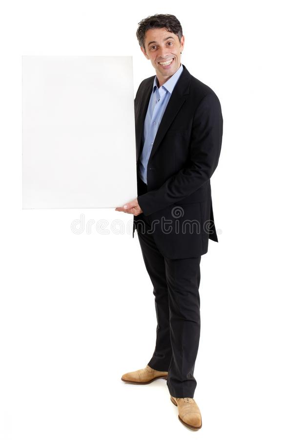 Salesman with a cheesy grin and a blank board. Stylish middle aged businessman or salesman with a cheesy friendly grin standing holding a blank white board for stock photos