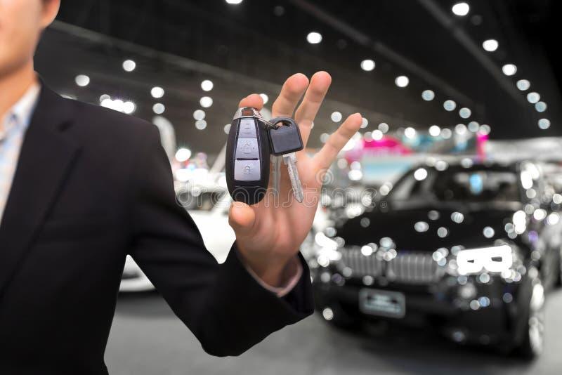 Salesman or dealer offering car keys to new owner in showroom, b royalty free stock image