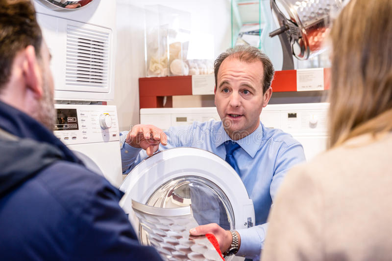 Salesman Explaining Product To Couple In Hypermarket royalty free stock photo