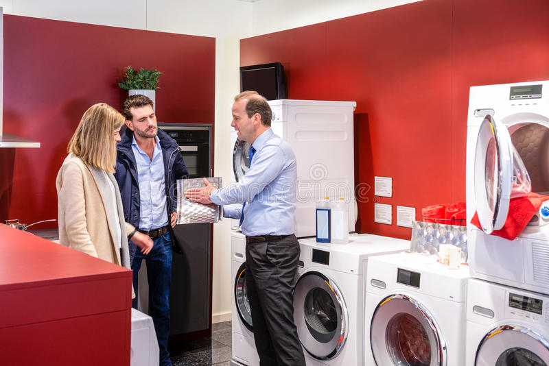 Salesman Explaining To Couple In Washing Machine Department stock photos
