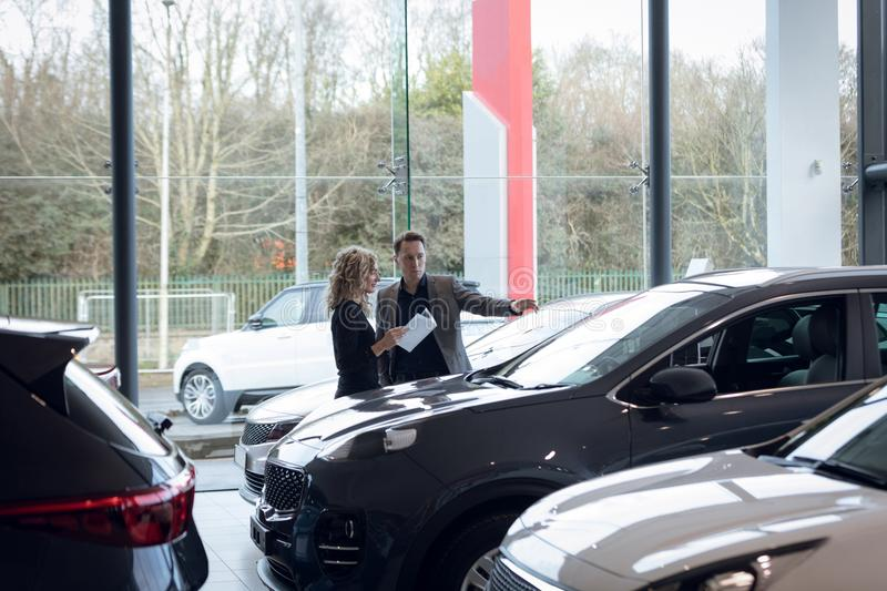 Salesman with female customer in car showroom. Salesman with female customer holding document while standing in car showroom stock photography