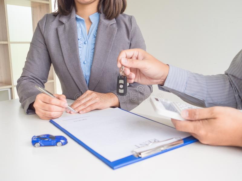 Salesman give key to customer Business woman after signed  a car rent service lease contract royalty free stock photography