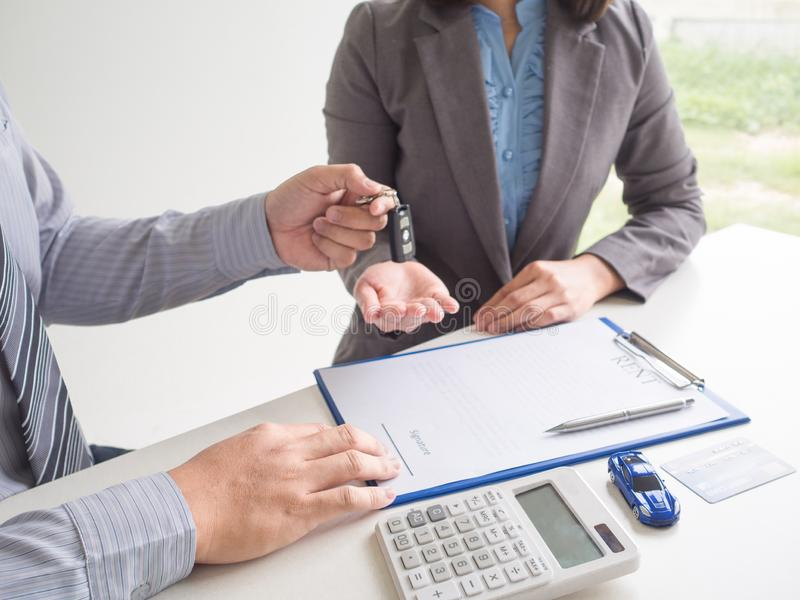 Salesman give key to customer Business woman after signed  a car rent service lease contract. Salesman give key to customer Business women after signed  a car royalty free stock image