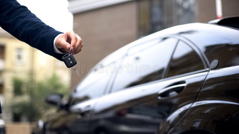 Salesman giving car key to buyer, dealership showroom, auto rental, luxury royalty free stock images