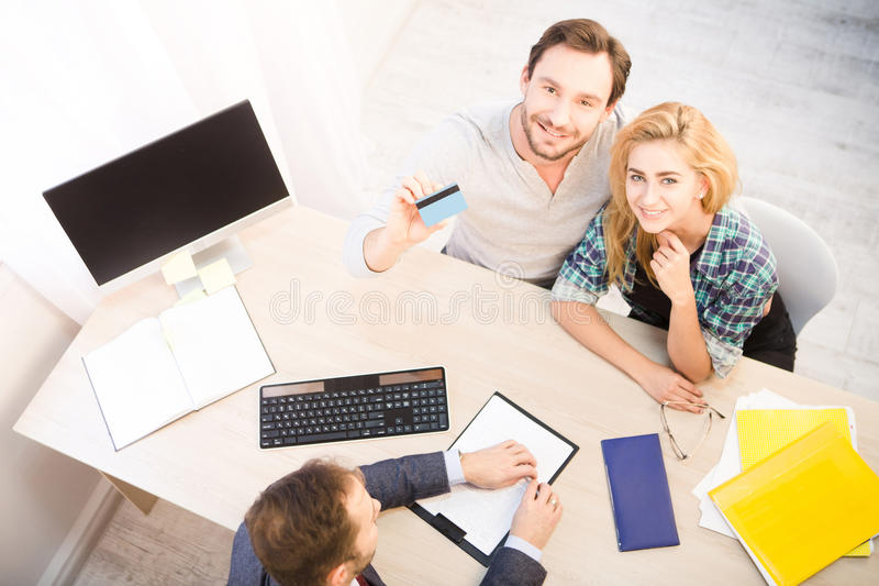 Salesman giving credit card. Dealership concept. Bank concept. Money concept. Top toned of happy couple showing their positive impression from getting credit stock photo