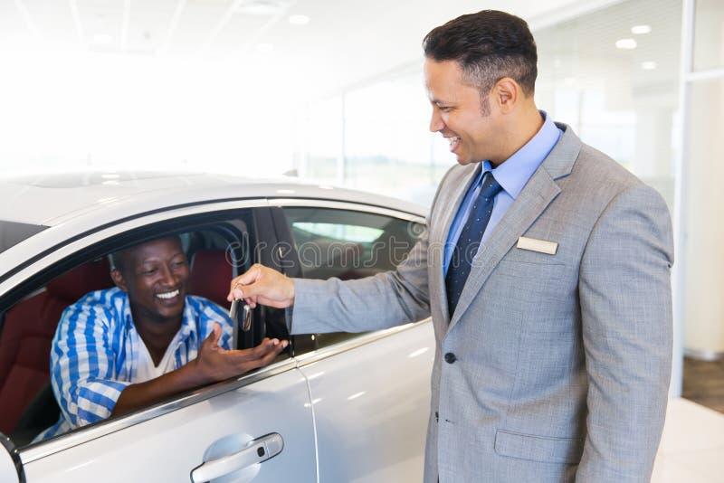 Salesman handing car key customer. Car salesman handing over new car key to customer sitting inside vehicle at showroom royalty free stock photos