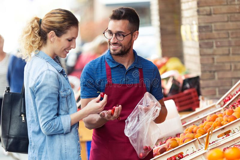 Salesman helping customer to choose some types of fruits in health grocery shop. royalty free stock photos