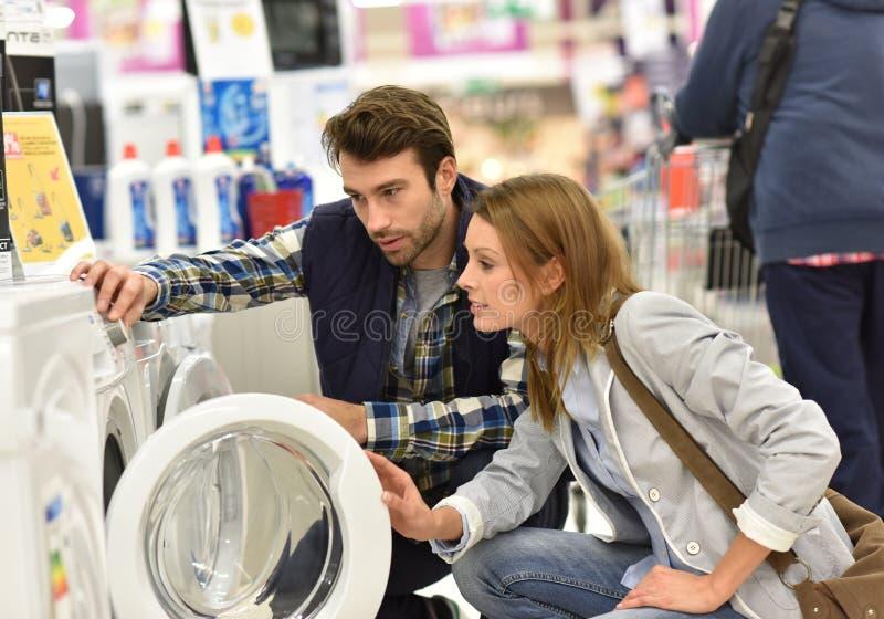 Salesman helping young customer on choosing washing machine stock photo