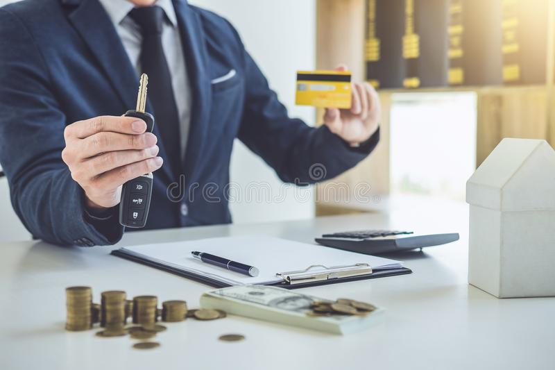 Salesman holding a key, credit card and calculating a price of s royalty free stock photo