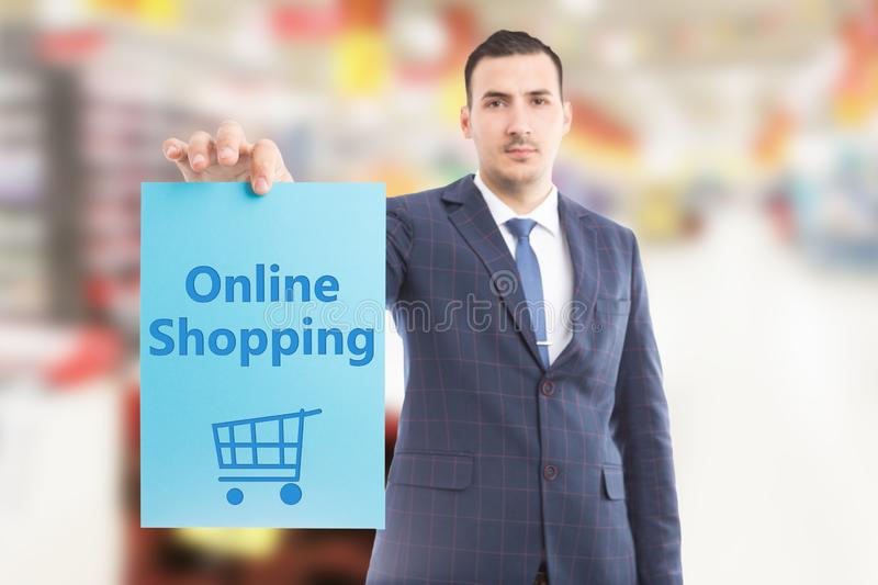Salesman holding online shopping paper. Salesman wearing suit and tie holding online shopping blue paper in hand with cart drawing as digital commerce concept royalty free stock image