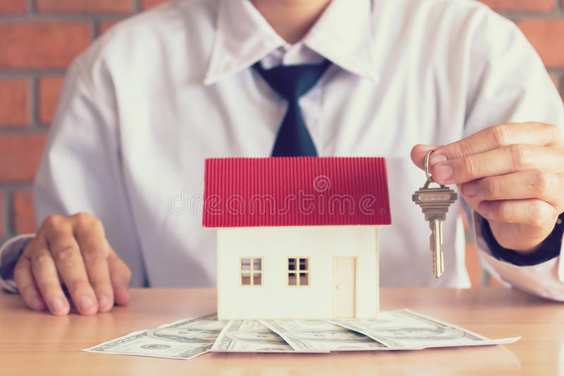 Salesman home brokers holding key to new homeowners customer. stock photography