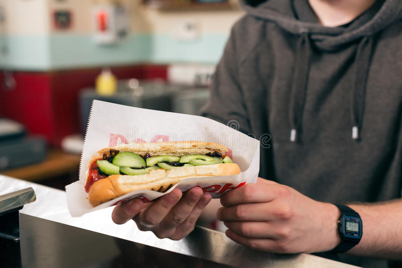 Salesman with hotdog in fast food snack bar stock photo