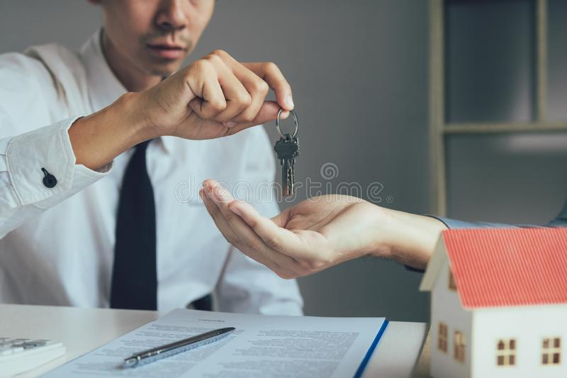 Salesman house brokers provide key to new homeowners in office.  stock photography