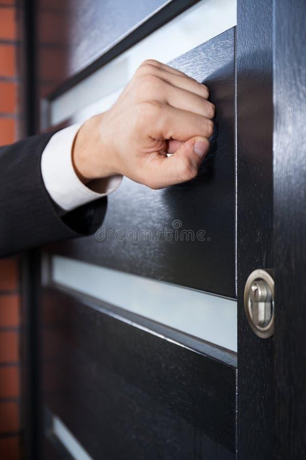 Salesman knocking on the door. Door to door salesman knocking on the door stock photography
