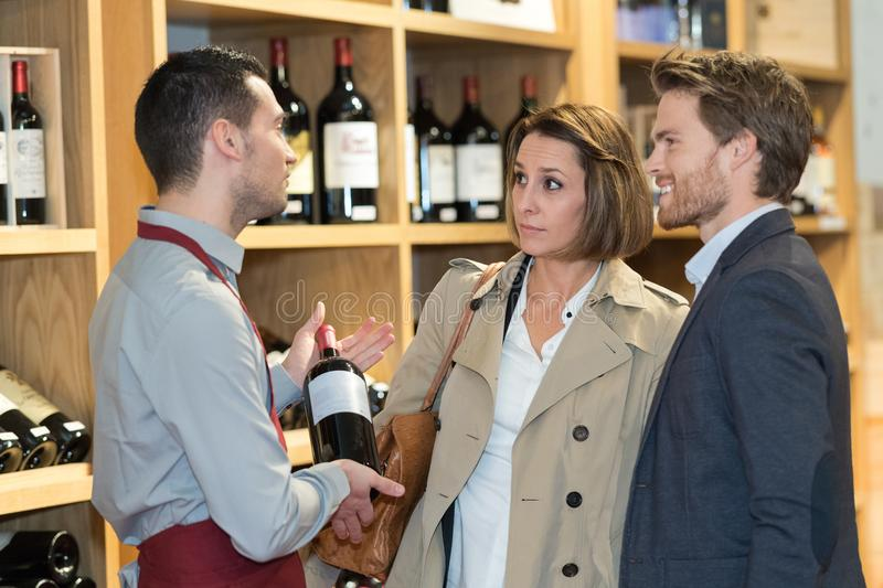Salesman offering bottle red wine to young couple. Salesman offering bottle of red wine to young couple stock photography