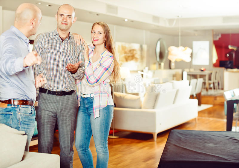 Salesman offering furniture to family couple stock image