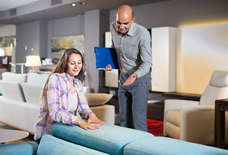 Salesman offering furniture variants to woman in salon. Adult salesman offering furniture variants to happy women in salon stock photos