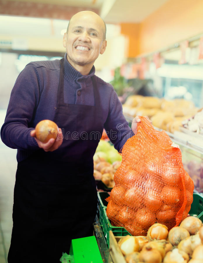 Salesman offering large onion royalty free stock image
