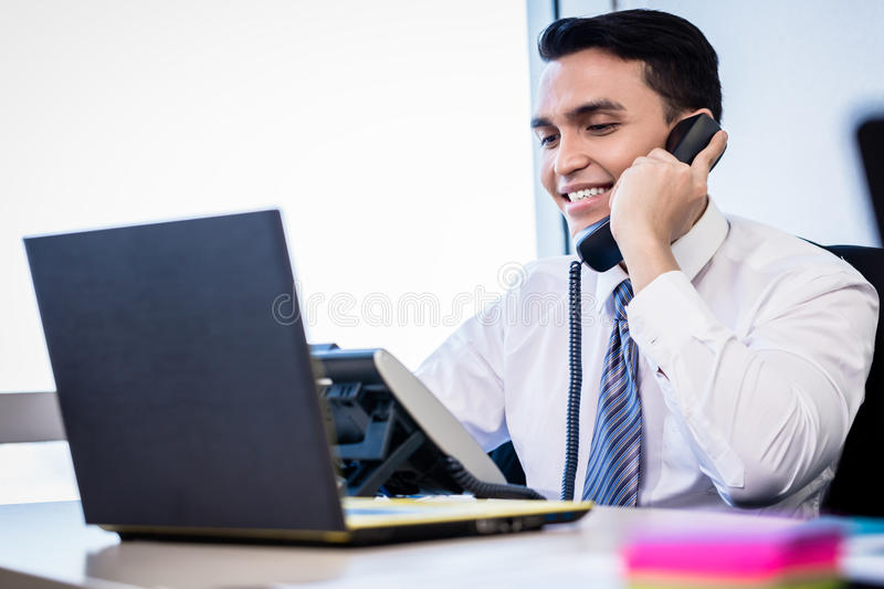 Salesman in office making phone call stock photo