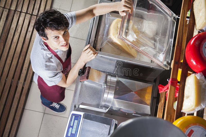 Salesman Packing Cheese In Vacuum Machine At Grocery Store royalty free stock image