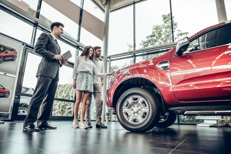 Salesman presenting special offers to clients. Car salesman showing new vehicle to family customers. bottom view royalty free stock image