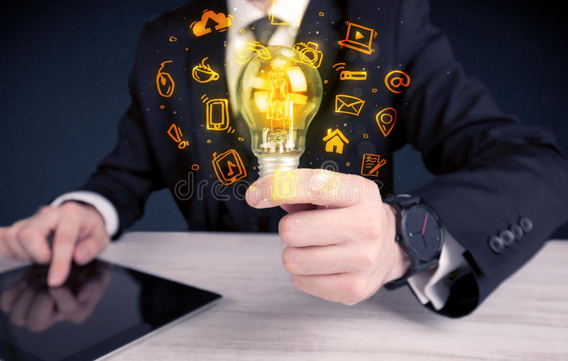 Salesman promoting his bright ideas. An office salesman promoting his bright ideas concept with illustration of online media and device logos around electric stock image