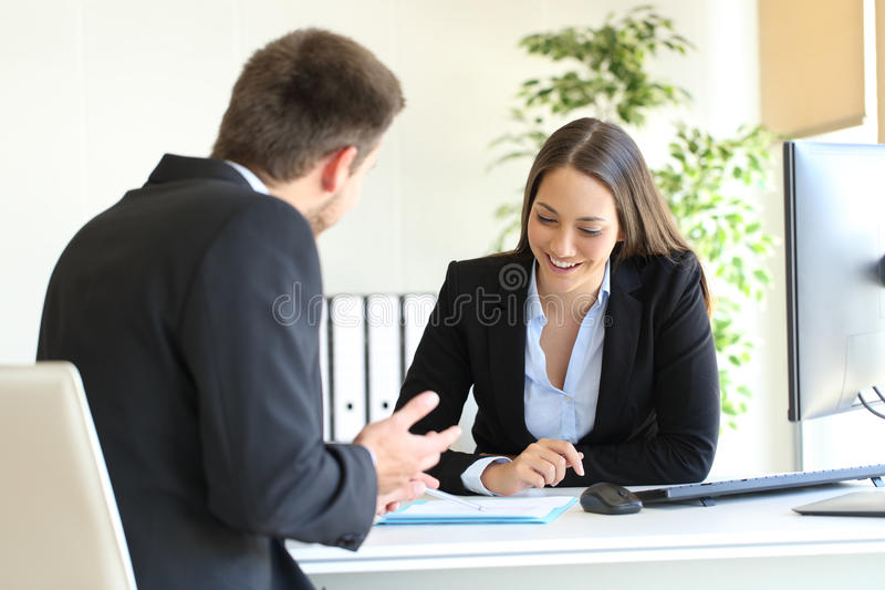 Salesman selling to a client at office royalty free stock photography