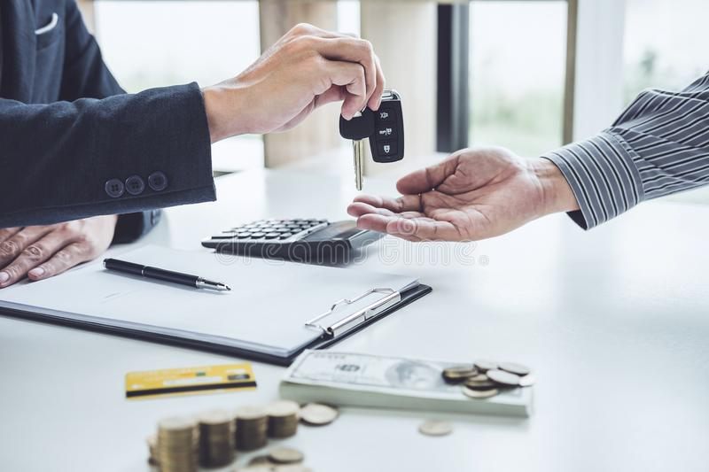 Salesman send key to customer after good deal agreement, success. Ful car loan contract buying or selling new vehicle royalty free stock photo