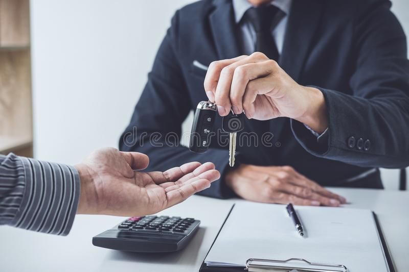 Salesman send key to customer after good deal agreement, success. Ful car loan contract buying or selling new vehicle royalty free stock images