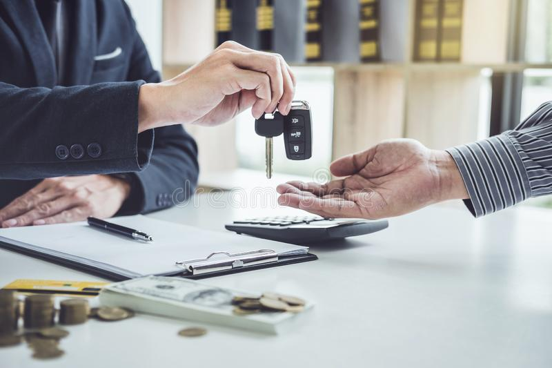 Salesman send key to customer after good deal agreement, success. Ful car loan contract buying or selling new vehicle royalty free stock photography