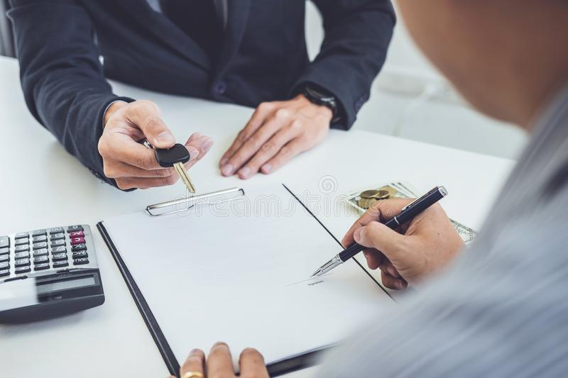 Salesman send key to customer after man signing car document contract good deal agreement, successful car loan contract buying or stock photography