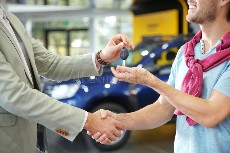 Salesman shaking hands with customer while giving car key in auto dealership. Closeup stock photo