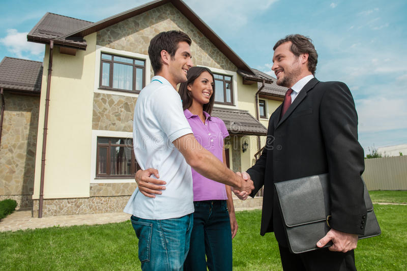 Salesman shaking hands with property owners. stock photos
